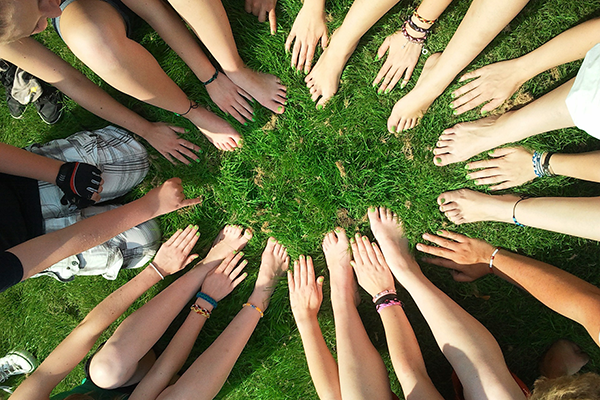 A circle of people in a circle putting their hands on the grass in the centre, depicting a community